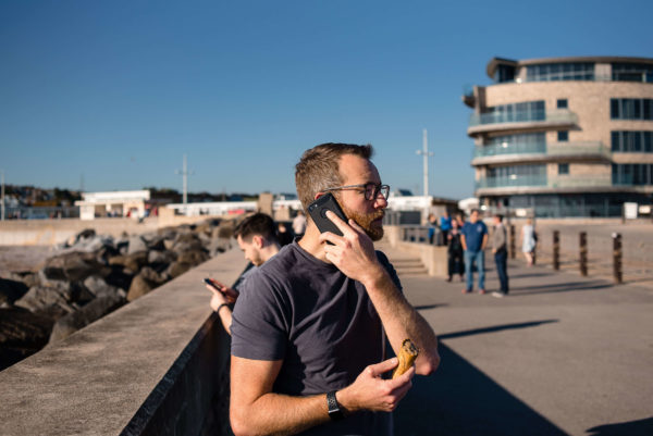 Joel Nurser, Operations Director at Composite Profiles, enjoying an ice cream whilst on the phone in West Bay, Dorset as part of their Building Excellence Strategy Day